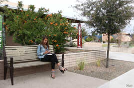 French international student Emma Seguy sits outside at the Mesa Community College campus in Mesa, Arizona.
