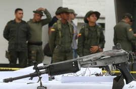 Police officers stand behind a seized weapon at the police station in Necocli, Colombia, March 11, 2015.