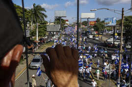 An individual watches from above as people march in an anti-government protest in Managua, Nicaragua, Aug. 11, 2018. The current unrest began in April, when President Daniel Ortega imposed cuts to the social security system and small protests by seni...
