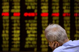 A Chinese investor monitors stock prices at a brokerage house in Beijing, Sept. 15, 2015.