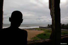 FILE - A young boy looks out from the window of his dilapidated home on the beach facing the Atlantic Ocean where his family lives in Monrovia, Liberia.
