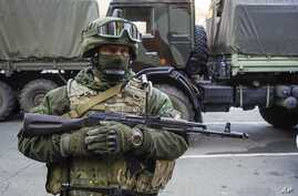 A Russia-backed rebel stands on guard during preparation for an exchange of prisoners in Donetsk, eastern Ukraine, Oct. 29, 2015.