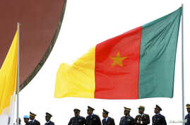 FILE - Cameroonian police stand near a national flag.