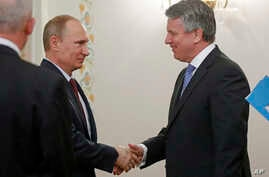 Russian President Vladimir Putin (l) shakes hands with Royal Dutch Shell's CEO Ben Van Beurden during their meeting in the Novo-Ogaryovo residence outside Moscow, April 18, 2014.