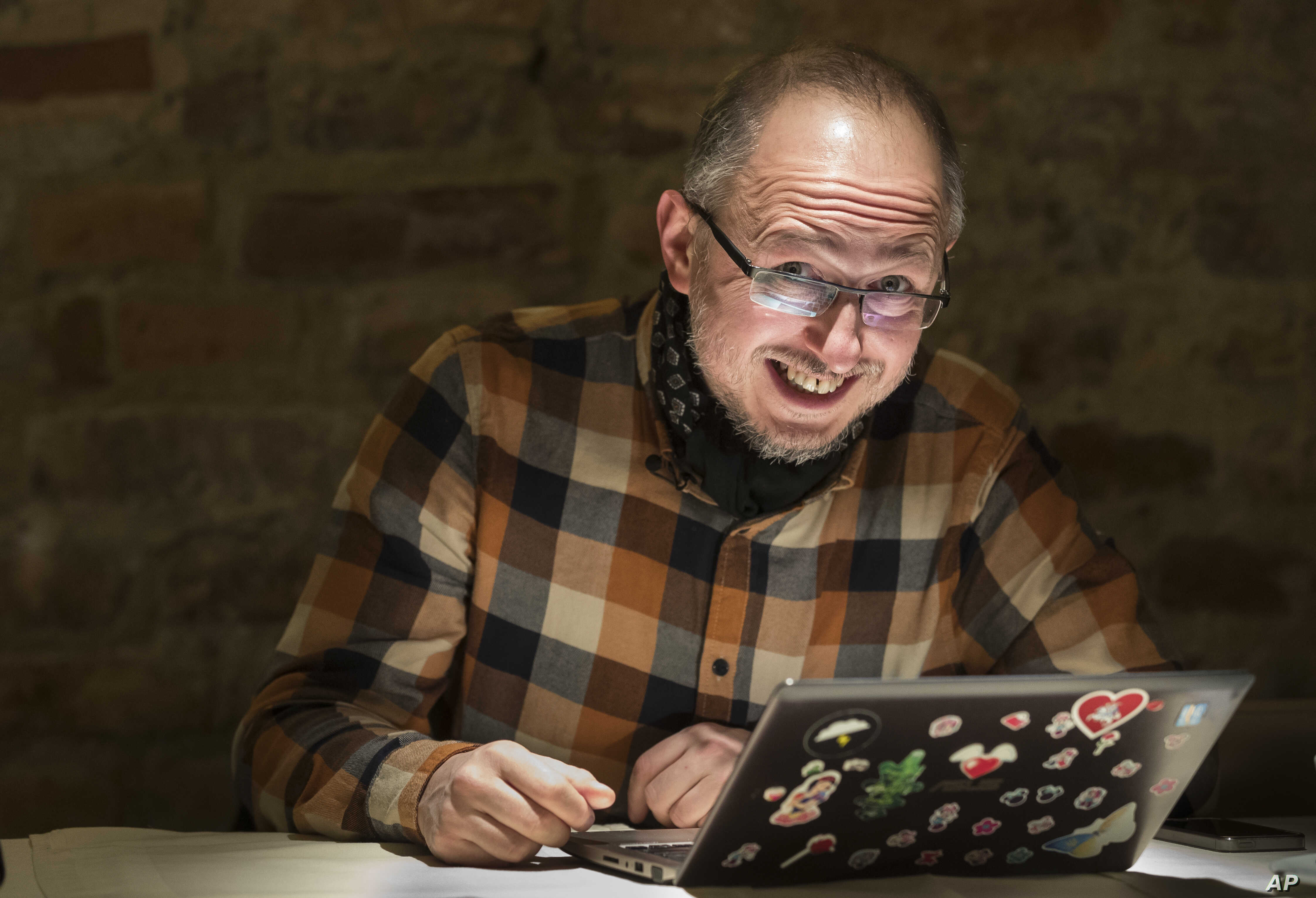 """In this Nov. 30, 2016 photo, Ricardas Savukynas, works on his computer in Vilnius, Lithuania. Savukynas is one of the Lithuanian volunteers who've dubbed themselves """"elves"""" patrol social media to expose fake accounts they accuse of spreading pro-Russ"""