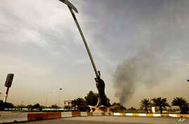 Black smoke from a car bomb attack is seen from the the Crossed Words monument in Baghad, Iraq, March, 14, 2013.