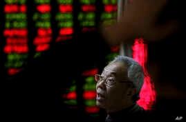 A man chats with other investors near an electronic board displaying stock prices at a brokerage house in Beijing, Jan. 5, 2016.