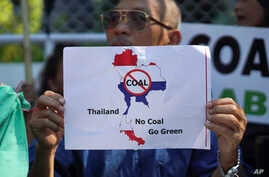 A man holds up a sign protesting against a proposed coal-fired plant on Thailand's coast, in Bangkok, Thailand, Feb. 17, 2017. The Thai government has put on hold construction of the plant near the pristine beaches on the Andaman Sea.