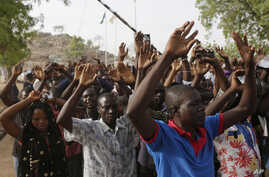 People displaced following attacks by Islamist militants raise their arms as they pass through security before casting their votes, in Yola, Nigeria, March 28, 2015.