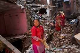 Nepalese women remove debris searching their belongings from their house that was destroyed a week ago during the earthquake in Bhaktapur, Nepal, Sunday, May 3, 2015.