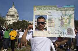 "Roberto Morales, 25, holds a sign representing a permanent resident card, while attending the ""All in for Citizenship"" rally in support of immigration reform in Washington, on April 10, 2013."