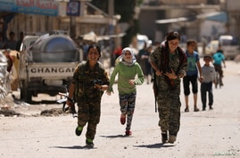 Syrian Democratic Forces female fighters run with children in the town of Tabqa, Syria, after SDF captured it from Islamic State militants this week, May 12, 2017.