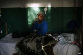 FILE - A teenage malaira patient sits in a bed at a hospital in Gao, northern Mali, Feb. 11, 2013.