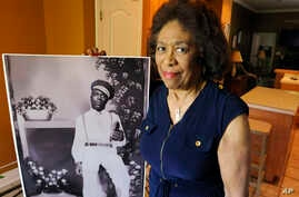 Josephine Bolling McCall poses with a photo of her father, lynching victim Elmore Bolling, at her home in Montgomery, Alabama, April 18, 2018. Bolling is among thousands of lynching victims remembered at the new National Memorial for Peace and Justic