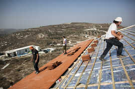 Men work on the roof of a house under construction in the unauthorised Jewish settler outpost of Havat Gilad, south of the West Bank city of Nablus, Nov. 5, 2013.