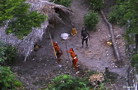 FILE - Members of an uncontacted Amazon Basin tribe and their dwellings are seen during a flight over the Brazilian state of Acre along the border with Peru in this May, 2008 photo distributed by FUNAI, the government agency for the protection of ind