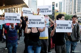 """Residents hold up signs that read, """"Metro workers: The people support you,"""" outside Ana Rosa subway station during the fifth day of metro worker's strike in Sao Paulo, Brazil, June 9, 2014."""