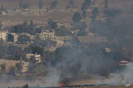 Smoke and fire rise in the Quneitra province as Syrian rebels clash with President Bashar Assad's forces, as seen from the Israeli controlled-Golan Heights, Wednesday, Aug. 27, 2014. Syrian rebels, including fighters from an al-Qaida-linked group, se