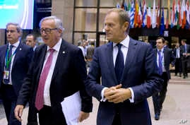 European Commission President Jean-Claude Juncker, center left, and European Council President Donald Tusk, center right, walk through the atrium during an EU summit in Brussels Oct. 19, 2017.