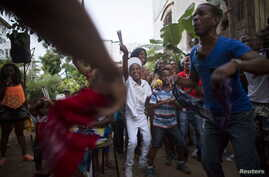 Yensy Villarreal, 9, (C), who lives in Miami, dances in the backyard of his home with friends in celebration for becoming a Santero after passing a year-long rite of passage in the Afro-Cuban religion Santeria, Havana, Cuba, July 5, 2015.