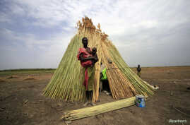 A woman from the Dinka tribe stands in front of her shelter near Bor, Jonglei state, in South Sudan, March 31, 2012.