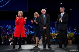 From left, Hillary Clinton, Iowa Democratic Chairwoman Andy McGuire, Bernie Sanders and Martin O'Malley greet the crowd at the Jefferson-Jackson Dinner in Des Moines, Iowa, Oct. 24, 2015.