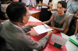 Myanmar opposition leader Aung San Suu Kyi, right, submits her documents for the upcoming general election at an election commission office on July 29, 2015, in outskirts of Yangon, Myanmar.