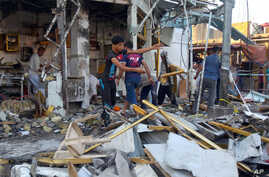 Shop owners clean up debris in the aftermath of a deadly car bomb explosion in a busy commercial district of al-Zubair, a suburb of the predominantly Shiite city of Basra, 340 miles (550 kilometers) southeast of Baghdad, Iraq, Tuesday, Oct. 6, 2015.