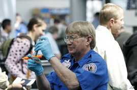 A TSA agent looks over a license at a security check point.