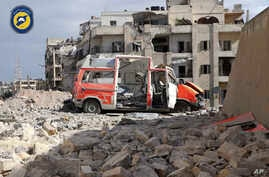 "In this photo provided by the Syrian Civil Defense group known as the ""White Helmets,"" a destroyed ambulance is seen outside the Syrian Civil Defense main center after airstrikes in Ansari neighborhood in the rebel-held part of eastern Aleppo, Syria,"