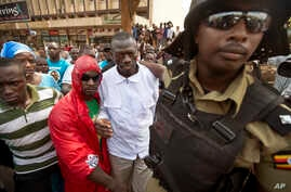 Leading opposition leader and presidential candidate Kizza Besigye, center, is arrested by riot police after attempting to walk with his supporters along a street in downtown Kampala, Uganda Monday, Feb. 15, 2016.