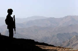 FILE - A Pakistani soldier stands guard along the border fence outside the Kitton outpost on the border with Afghanistan, in North Waziristan, Pakistan Oct. 18, 2017.