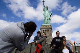 Tourists pose for photographs in front of the Statue of Liberty in New York Harbor in New York. The Statue of Liberty reopened to the public after the state of New York agreed to shoulder the costs of running the site during the partial federal gover