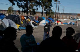 Men discuss rumors of other migrants who successfully snuck into the U.S. in a tent camp outside the closed Benito Juarez sports complex, in Tijuana, Mexico, Friday, Dec. 7, 2018.