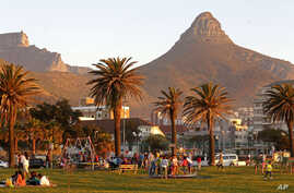 People enjoy sunset on a grass area well known for their walking trails in Cape Town, South Africa, Aug. 24, 2014.