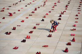 A display of hundreds of red shoes spread as protest against violence toward women in Israel at Habima Square in Tel Aviv, Israel, Tuesday, Dec. 4, 2018.