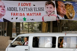 An Egyptian drives past banners supporting presidential candidate Abdel-Fattah el-Sissi in Cairo, Egypt,  May 27, 2014.