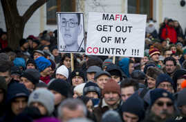 FILE - People march in silent protest in memory of murdered journalist Jan Kuciak and his girlfriend Martina Kusnirova in Bratislava, Slovakia, Feb. 28, 2018. In the wake of an unprecedented slayings of an investigative journalist and his fiancee, Sl