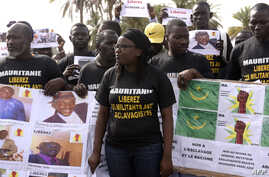 "FILE - Anti-slavery militants hold a banner whose message translates as ""No to slavery and racism, no to the regime of the general dictator slavery racist Mohamed Ould Abdel Aziz"" demonstrate, Aug. 3, 2016, in Dakar against the imprisonment of fellow"