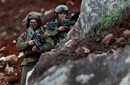 Israeli soldiers stand guard at the site of their excavation work, near the southern border village of Mays al-Jabal, Lebanon, Dec. 13, 2018.