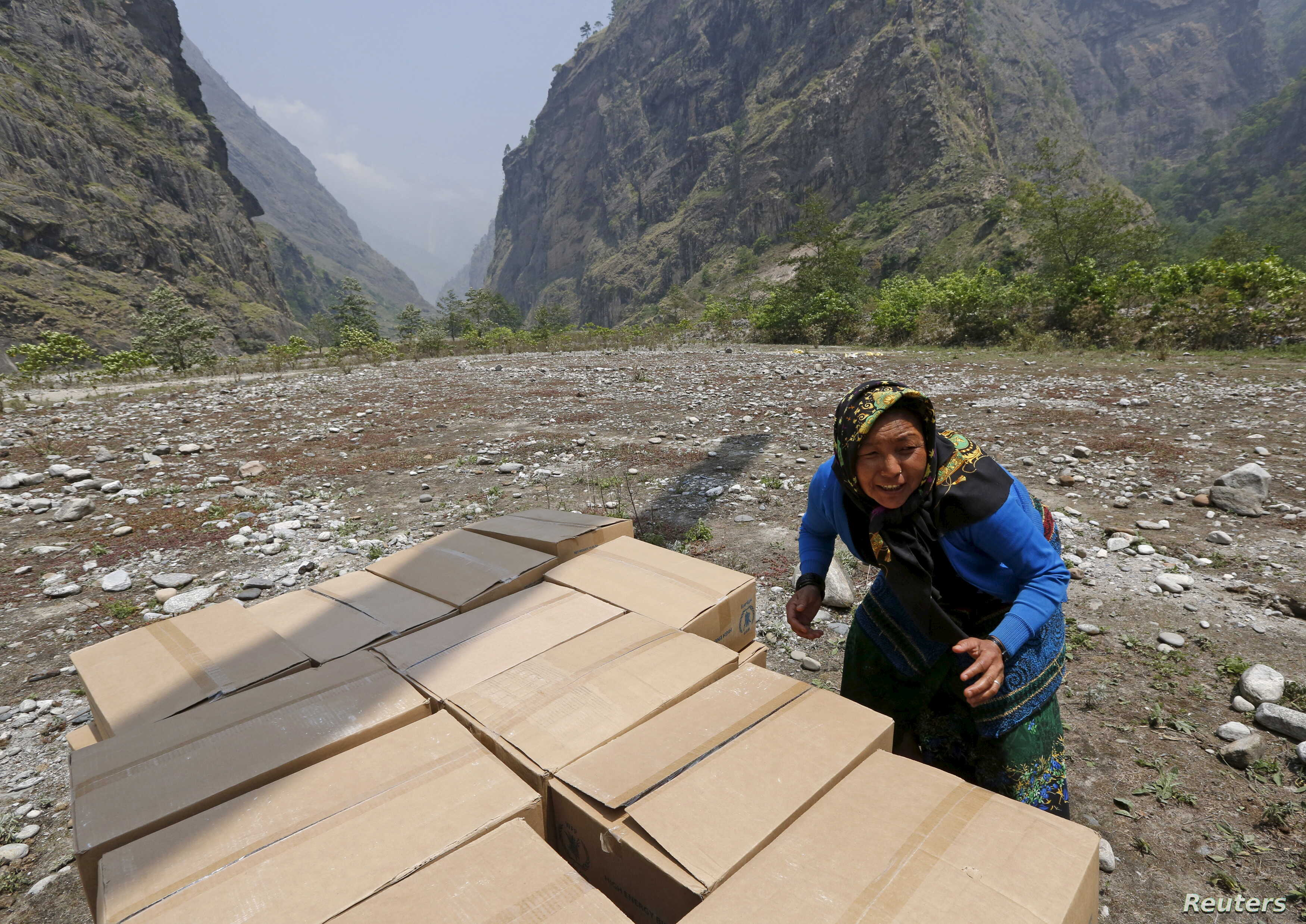 A woman helps unload emergency food supplies after the April 25 earthquake in Dovan, Nepal, May 8, 2015. REUTERS/Olivia Har