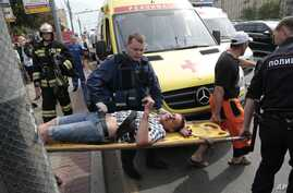 Paramedics and a police officer carry an injured man out from a subway station after a rush-hour subway train derailment in Moscow, Russia, July 15, 2014.