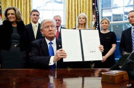 President Donald Trump holds up a signed executive order in the Oval Office of the White House in Washington, Jan. 28, 2017.