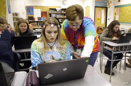FILE — Teacher Carol Mowen, right, works with student Kirs