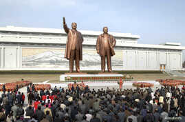 North Korean soldiers, workers and students place flowers before the statues of North Korean founder Kim Il-sung (L) and his son, late leader Kim Jong-il, on the 101st anniversary of Kim Il-sung's birth, at Mansudae in Pyongyang, in this photo distri