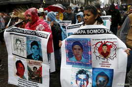 Relatives and friends hold banners with images of some of the 43 missing students of Ayotzinapa College Raul Isidro Burgos as they march in Mexico City to mark the first anniversary of the students' disappearance, Sept. 26, 2015.