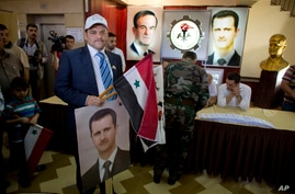 A man holds a portrait of President Bashar al-Assad and a national flag at a polling station in Damascus, June 3, 2014.
