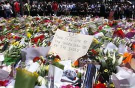 Members of the public stand behind a note that can be seen amongst floral tributes that have been placed near the cafe where hostages were held for over 16-hours, in central Sydney December 16, 2014. Heavily armed Australian police stormed a Sydney c