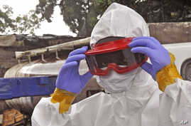 A Liberian health worker prepares his protective gear before removing the body of a man that they believe died from the Ebola virus in Monrovia, Aug. 29, 2014.