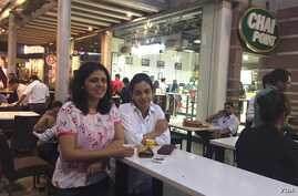 Sonal Jain (left in white shirt) takes a break from office to relax over a cup of tea with a friend. (A. Pasricha/VOA)